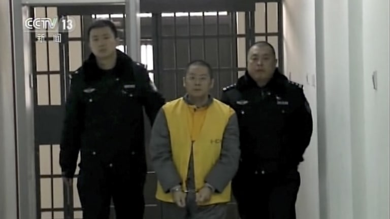 Ding Ning, owner of Ezubao, is escorted by policemen in an unknown location in this image taken from CCTV footage.