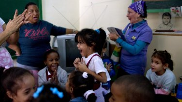 Students and teachers celebrate after listening to a live, nationally broadcast speech by Cuba's President Raul Castro about the country's restoration of relations with the United States, at a school in Havana, Cuba.