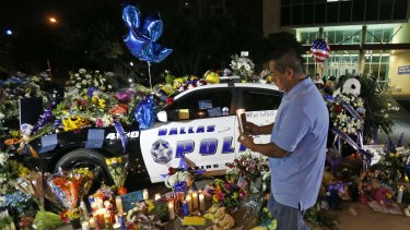 Alejandro Rodriguez places a candle in front of police cars decorated as a public memorial outside Dallas police headquarters, in memory of police who were shot Thursday in the city.