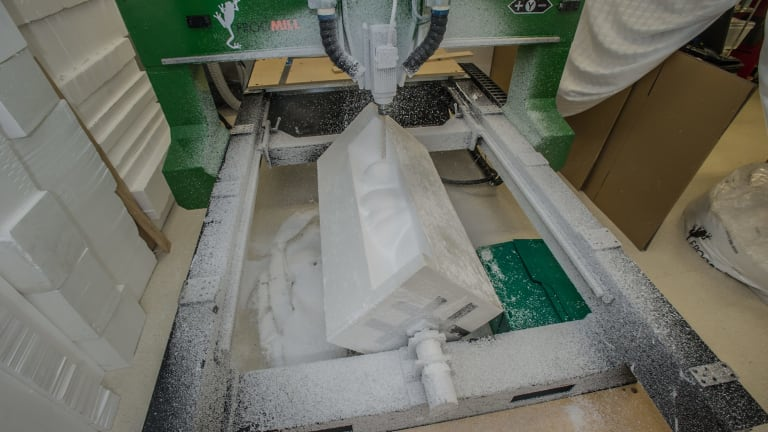 The CNC machine in action, carving a size 18 body from a block of foam.