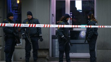 Police officers control the street in front of an internet cafe in Norrebro district in Copenhagen.