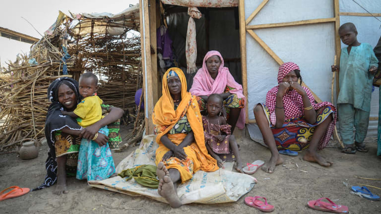 A family at Goni Kachallari in Maiduguri. They are one of 17,700 families in Borno who receive a monthly ration of oil, beans and millet.