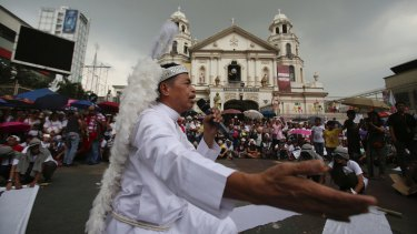 A protester dressed as a priest performs during a Christmas-theme street play to protest alleged extra-judicial killings in Manila.