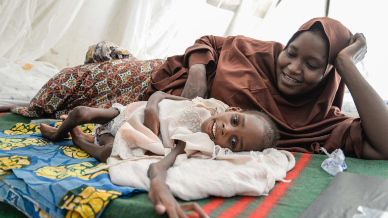 Amina, 8, weighs 7.2kg. She suffers from severe acute malnutrition accompanied by severe diarrhea and has chronic cerebral palsy. Pictured with her mother, Amina, Amina is being fed at MSF's Gwange therapeutic feeding centre.