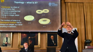 Professor Thors Hans Hansson gives a demonstration after revealing the winners of the Nobel prize in physics in Stockholm.