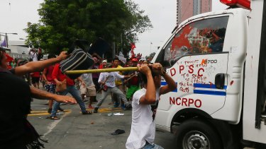 Protesters hit a Philippine National Police van after it rammed into protesters outside the US embassy in Manila on Wednesday.