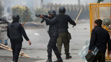 A Pakistani police officer aims his gun towards the protesters during a clash in Islamabad.