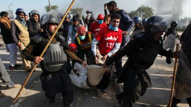 A protester is carried off by police, who have attempted to disperse a blockade of a main route into Islamabad.