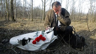 Polish Ian Grushinski grieves by a piece of the wreckage at a plane crash site near Smolensk on Sunday, April 11, 2010.
