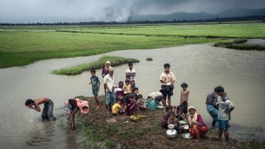 Rohingya refugees rest near the Naf River separating Myanmar and Bangladesh after crossing the border this month.