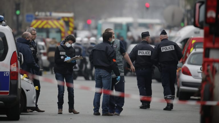 Forensic investigators examine the area near <i>Charlie Hebdo</i>'s Paris office after the January attack.