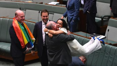 Liberal MP Warren Entsch lifts Labor MP Linda Burney into the air after the same-sex marriage vote in the House of Representatives.