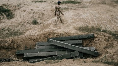 An Iraqi army soldier walks past discarded empty rocket boxes outside Makhmour in March.