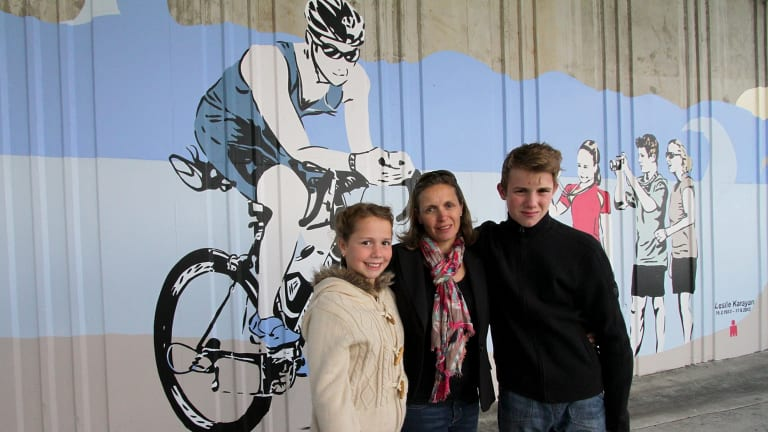 Les Karayan's wife Kerri and children Sabine, 10, and Alessandro, 13, stand in front of the commemorative mural that depicts their dad.