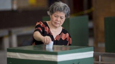 A voter casts a ballot in Bangkok.
