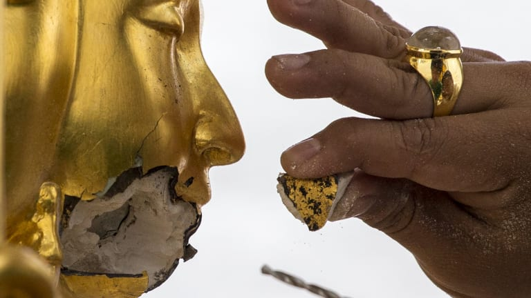 A craftsman fixes the statue of Hindu god Brahma after it was damaged during the deadly blast at the Erawan shrine.