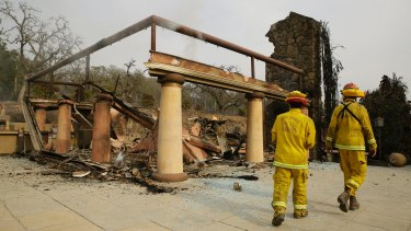 A pair of Napa County firefighters walk through the remains of the Signorello Estate winery on Tuesday.