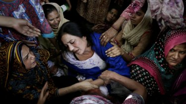 Women try to comfort a mother who lost her son in the attack.
