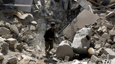 A police trooper walks through a crater left by an air strike on houses near Sanaa Airport.