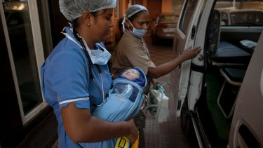 A newborn baby is transferred to an ambulance from a clinic in Anand, India, which has also banned surrogacy services for foreigners.