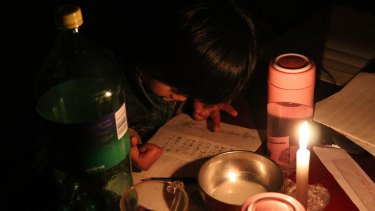Xu Yuanyuan doing her homework by candlelight at Picun Village in Beijing.