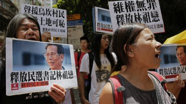 Protesters hold pictures of the Wukan village's 70-year-old leader, Lin Zuluan, during a protest in Hong Kong on Tuesday.