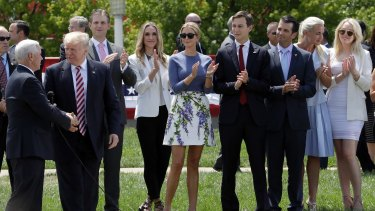 Donald Trump shakes now Vice-President Mike Pence's hands as his sons Eric, daughter-in-law Lara Yunaska, daughter Ivanka, Ivanka's husband Jarred Kushner, son Donald jnr and wife Vanessa, and daughter Tiffany look on during the campaign.
