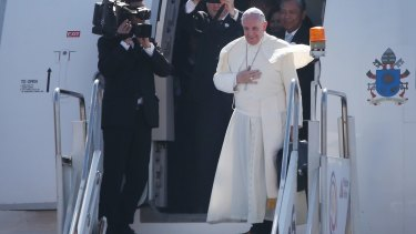 Pope Francis waves from the steps of his aircraft as he leaves the Philippines for Rome on Monday.
