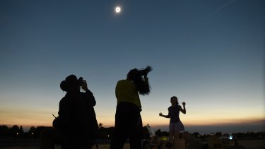 Julian Ledger, of Los Angeles, photographs the solar eclipse in Albany, Oregon.