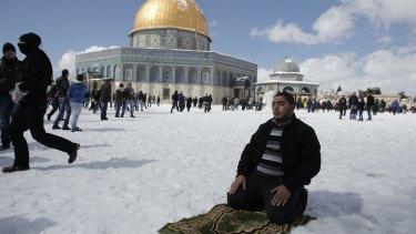 A man prays in the snow.