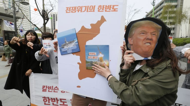 A South Korean protester holds a mask of US President Donald Trump and a Korean Peninsula map during a rally against US deployment in the region outside the US embassy in Seoul.
