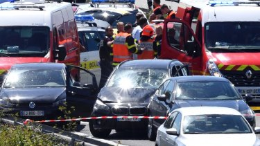 French security forces and emergency vehicles surround a car that authorities say was used in an attack on soldiers.
