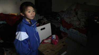 """Xu Tingting, 9, in her family's one-room apartment. Picun Village, on the eastern outskirts of Beijing, is home some 20,000 """"migrant workers""""."""