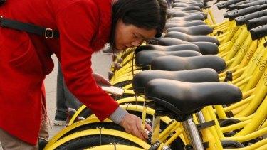 A Beijing commuter unlocks her share bike.