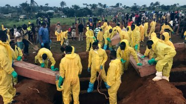 Volunteers handle a coffin during a mass funeral for victims of heavy flooding and mudslides in Regent at a cemetery in Freetown, Sierra Leone. Churches across Sierra Leone held special services Sunday in memory of the hundreds killed.