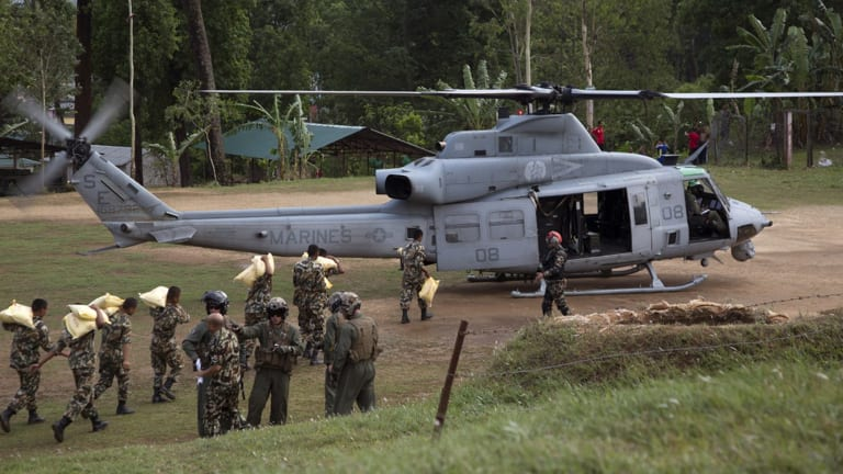 Nepalese service members load relief supplies into a US Marine Corps UH-1Y Venom from Joint Task Force 505 at Sindhuli, Nepal. A US Navy helicopter has gone missing, with six US Marines and two Nepalese soldiers aboard, following the second earthquake.