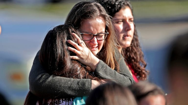 Students released from a lockdown embrace following the shooting.