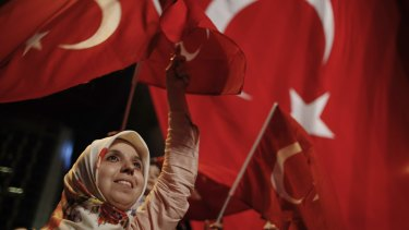 A woman waves Turkish flags during a rally against the attempted coup in Istanbul on Monday.