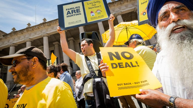 Taxi drivers Aytac Arman (c) and Nirmal Singh Sekhon (r) protest on the steps of Parliament house on December 3, 2016 in Melbourne, Australia.