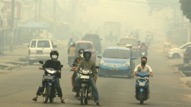 Motorists ride on a road as haze from wildfires blankets the city in Jambi, Indonesia.