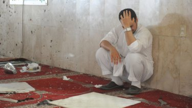 A family member of a slain victim mourns after a suicide bomber struck the Imam Ali mosque in Saudi Arabia in May.