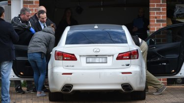 Police search a white Lexus parked in the driveway of a home at Canley Vale.