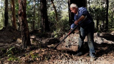Mark Leveson uses a metal detector at the search site.