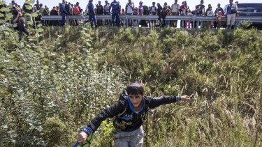 A boy flees a collection point set up to transport refugees to camps in Morahalom, Hungary.