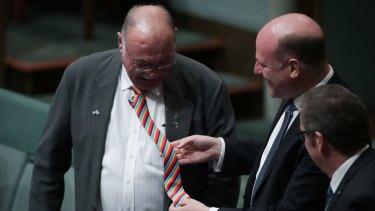 Liberal MP Trent Zimmerman looks at Warren Entsch's rainbow tie.
