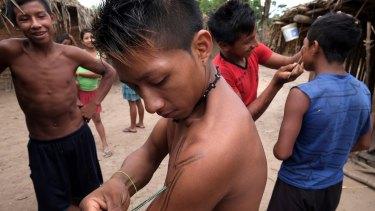 Young men apply ink to their skin in Awa Village.