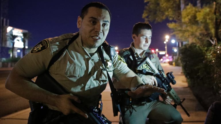 Police officers tell people to take cover after shootings in Las Vegas.