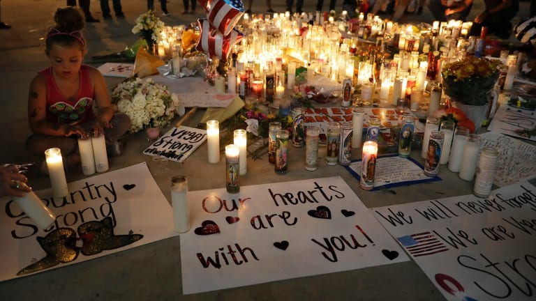 A girl places candles at a memorial in Las Vegas.