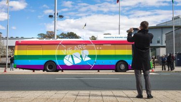 Minster for Road Safety Shane Rattenbury takes a photo of a bus newly painted in rainbow colours in support of marriage equality on Tuesday.