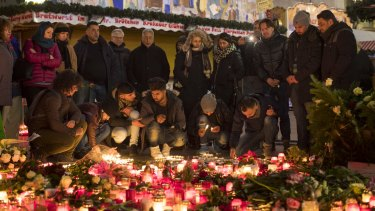 People light candles as floral tributes sit in Berlin Christmas market after a terror attack last year.